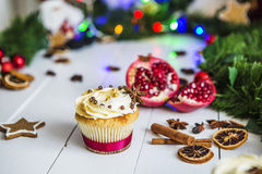 Cream cakes, cupcakes cut red pomegranate, cinnamon, dried lemons lie on white wooden table Stock Image