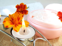 Cream and candle with flowers Stock Images