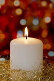 Cream candle with gold tinsel Stock Image