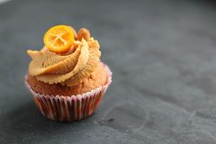 Cream caramel cupcake on black board decorated by almonds Royalty Free Stock Image