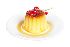 Cream caramel dessert with red currants. Close-up of a vanilla cream caramel dessert with red currants on white dish. Shallow depth of field Royalty Free Stock Photo