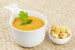 Cream of carrot soup and bread croutons Royalty Free Stock Images