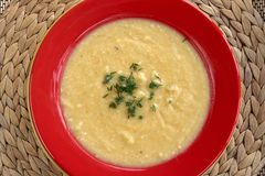 Cream of celeriac soup. Hot cream of celeriac soup in a red plate on the table. Best for autumn cold Stock Photography
