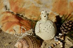 Cream ceramic snowman on beach sand shell pine cone african beads Christmas in July. Cream ceramic snowman on beach sand shell pine cone natural African beads Stock Photos