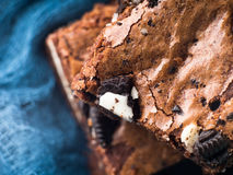 Cream cheese brownies with cookies on blue. Macro Stock Photography