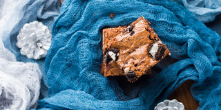 Cream cheese brownies with cookies on blue Royalty Free Stock Image