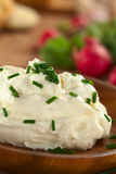 Cream Cheese with Chives. Fresh cream cheese spread on wooden plate with chives on top and radish in the back (Selective Focus, Focus on the chives on the top of Royalty Free Stock Photo