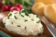 Cream Cheese with Chives. Fresh cream cheese spread on wooden plate with chives on top, radish and buns in the back (Selective Focus, Focus on the chives on the Royalty Free Stock Photos