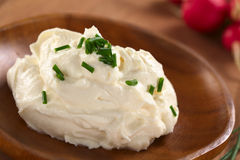 Cream Cheese. Fresh cream cheese spread on wooden plate with chives on top and radish in the back (Selective Focus, Focus on the chives on the top of the cream Royalty Free Stock Photos