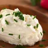 Cream Cheese. Fresh cream cheese spread on wooden plate with chives on top and radish in the back (Selective Focus, Focus on the chives on the top of the cream Stock Photos