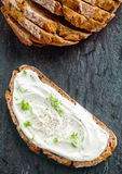 Cream cheese with herbs and seasoning. On a slice of fresh rye bread with the sliced loaf alongside, viewed from above with copyspace Stock Images