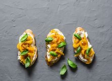 Cream cheese, roasted yellow bell pepper, basil bruschetta on  on grey background, top view. Copy space Stock Image