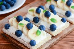 Cream cheese sandwiches idea. Vegetarian crusty bread sandwiches with cheese cream, bananas and berries on wooden board. Curd sandwich recipe. Cream cheese stock photos