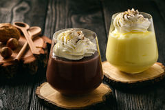Cream and chocolate pudding with whipped cream on wooden background. Stock Photography