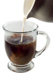Cream in coffee. Cream pouring into coffee in a clear mug isolated on white with clipping path Royalty Free Stock Photo