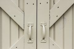 Barn doors and handles. Cream color wood barn doors and metal handles and cross bracing boards with nail heads showing royalty free stock images