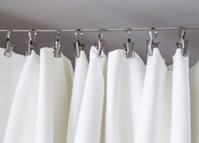 Cream-colored curtain hanging on a string on metal hooks illuminated by daylight. Cream-colored curtain hanging on a string on a metal hook in white ceiling Stock Photography
