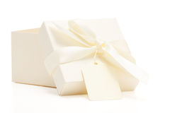 Cream colored gift box with bow and name tag Stock Photos