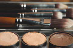 Cream concealer palette in metal case. Expensive makeup brushes made of special fibers to work with creamy textures Royalty Free Stock Image