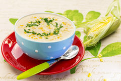 Cream of corn soup in blue bowl Stock Images
