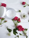 Cream facial cosmetic health nourishing fresh pink blossom white flowers white wooden. Cream cosmetic facial natural pink fresh rose white flowers white wooden Royalty Free Stock Image