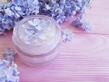 Cream cosmetic lilac flower on a pink wooden background therapy. Cream cosmetic lilac flower pink wooden background therapy stock image