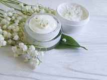 Cream cosmetic lily of the valley relaxation ointment aromatic rustic beauty on a white wooden background. Cream cosmetic lily of the valley white wooden royalty free stock photos