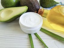 Cream cosmetic moisturizer health care avocado treatment ingredient oil on white wooden. Cream cosmetic avocado oil white wooden ingredient treatment health care Stock Image