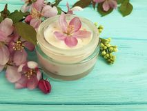 Cream cosmetic pink flowers on mint wood scrub, handmade royalty free stock image