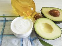 Cream cosmetic product green ingredient care healthy avocado oil yellow flower on white wooden. Cream cosmetic avocado oil yellow flower on white wooden bottle Royalty Free Stock Photos