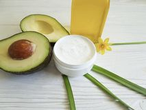 Cream cosmetic product ingredient care healthy avocado oil yellow flower on white wooden. Cream cosmetic avocado oil yellow flower on white wooden bottle product Stock Photo