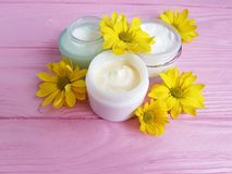 Cream cosmetic product yellow flowers pink wood background royalty free stock photos