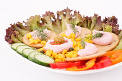 Cream on crackers. Cream, sweet corn and dill on crackers and vegetables in white plate Stock Photos