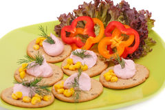 Cream on crackers. And vegetables on green plate Stock Image