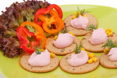 Cream on crackers. And vegetables on green plate Stock Photo