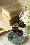 Cream de Cassis homemade blackcurrant liqueur in small glasses, books and flowers. Rustic style. royalty free stock image