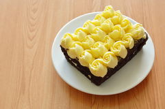 Cream decorate rose flower topping chocolate cake on plate. Cream decorate rose flower topping chocolate cake on white plate Stock Images