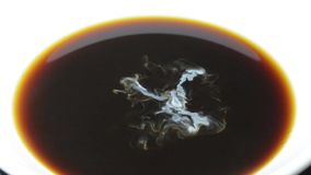 Cream drops fall into the cup of coffee close-up slow motion full-HD stock footage