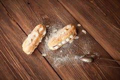 Cream eclairs с свежими полениками на деревянной таблице Стоковые Фото