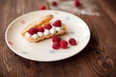 Cream eclairs с свежими полениками на плите на деревянной таблице Стоковое Изображение RF