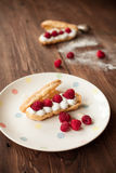 Cream eclairs with fresh raspberries, breakfast Royalty Free Stock Image