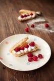 Cream eclairs with fresh raspberries, breakfast. Cream eclairs with fresh raspberries on table, breakfast Royalty Free Stock Image