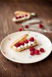 Cream eclairs with fresh raspberries, stilllife. Cream eclairs with fresh raspberries on table, stilllife Stock Photos