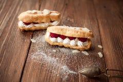 Cream eclairs with fresh raspberries on wood table. Cream eclairs with fresh raspberries on old wood table Stock Photo