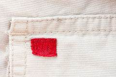 Cream fabric, red label and seam texture background Royalty Free Stock Images