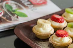 Cream filled tartlets. There are strawberries, kiwi and bananas stock photos