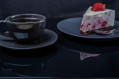 Cream fruit cake and a cup of black coffee on a black glass table stock photos