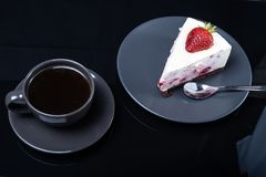 Cream fruit cake and a cup of black coffee on a black glass table stock photography