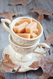 Cream fudge in mug. Cream fudge in vintage mugs on wooden table with fall leaves. Selective focus Stock Photography