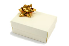 Cream Gift Box with Bow. Textured cream cardboard gift box with metallic gold coloured bow, isolated on white Royalty Free Stock Image